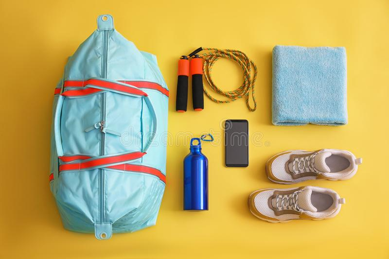 Gym bag, smartphone and sports equipment on background, flat lay. Gym bag, smartphone and sports equipment on yellow background, flat lay royalty free stock photography