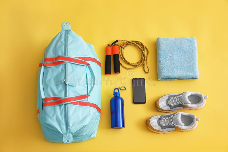 Gym bag, smartphone and sports equipment on background, flat lay. Gym bag, smartphone and sports equipment on yellow background, flat lay royalty free stock photos