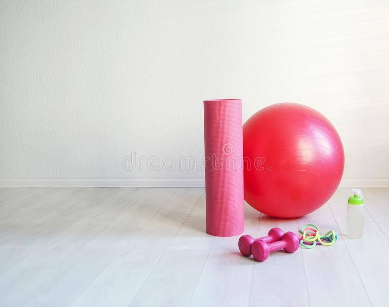 Gym ball, yoga mat, skipping rope, dumbbell and bottle of the w. Sports equipment. Gym ball, yoga mat, skipping rope, dumbbell and bottle of the water closeup on royalty free stock images