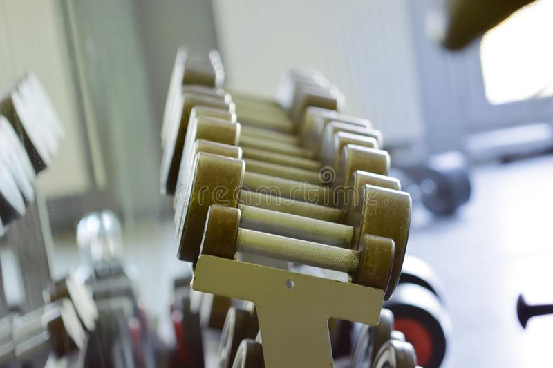 Gym Equipment - close up. Gym Equipment. Close up of dumbbells on rack in sport fitness center. Workout training and fitness gym concept. Sport equipment and stock images