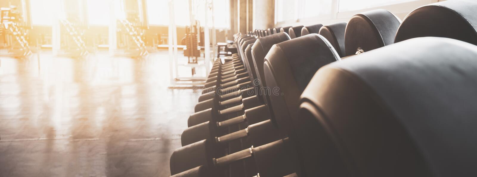 Gym equipment wide interior gym for fitness banner background close up dumbbells and blurred equipment royalty free stock photos