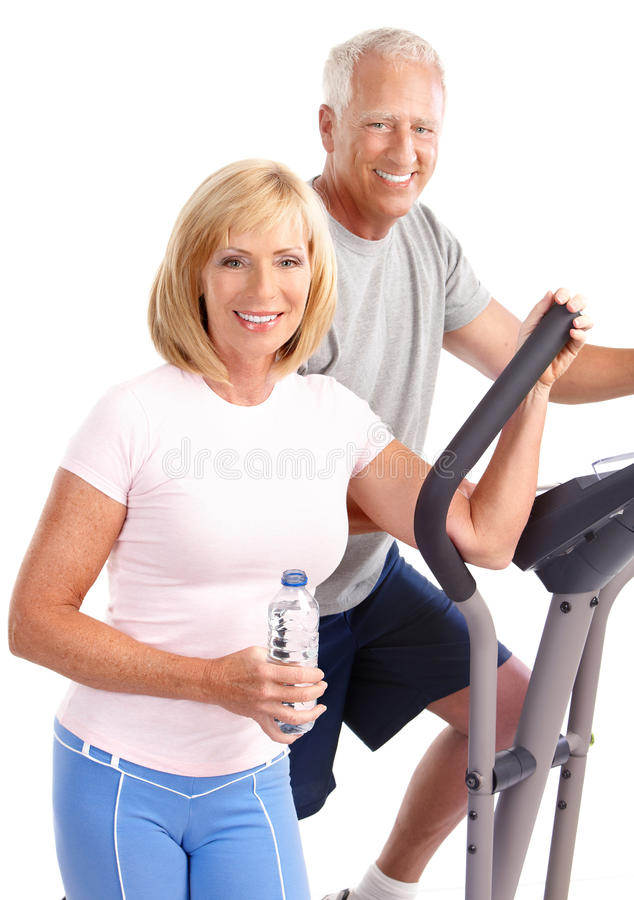 Gym & Fitness. Smiling elderly couple working out. Isolated over white background stock image