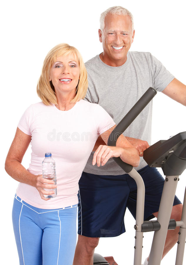 Gym & Fitness. Smiling elderly couple working out. Isolated over white background royalty free stock photography