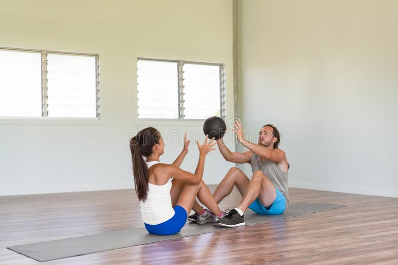 Gym fitness couple training body core together throwing weight ball at each other during sit-ups on floor workout exercise mat. Fun friends activity stock photography