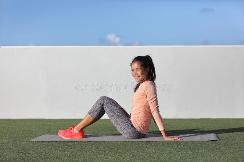 Gym fitness woman portrait relaxing on exercise mat in outdoor park grass. Happy Asian fit girl healthy active lifestyle ready for. Morning yoga practice royalty free stock image