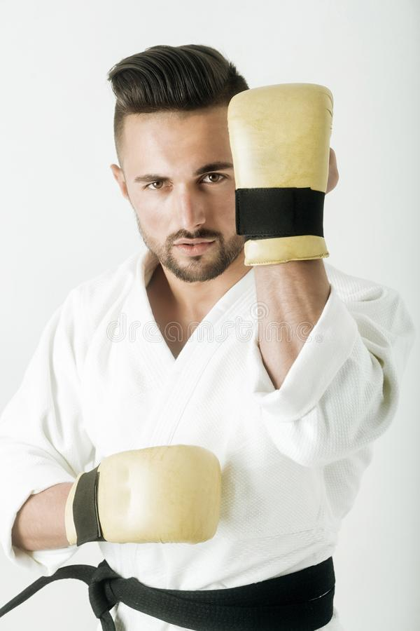 Gym, hall for karate. Oriental martial arts. Attractive warrior in kimono. Handsome sportsman with a beard. Defensive. Stand in martial arts. Strong bearded royalty free stock image
