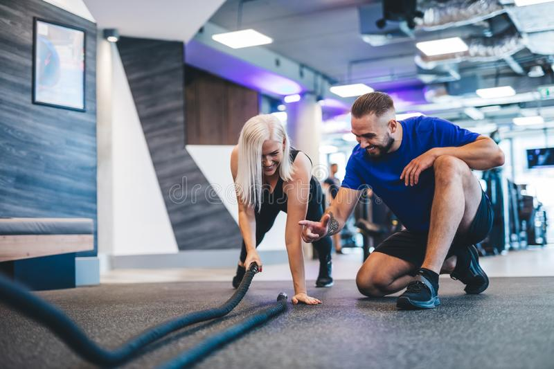 Gym instructor and a woman exercising at the gym. stock images