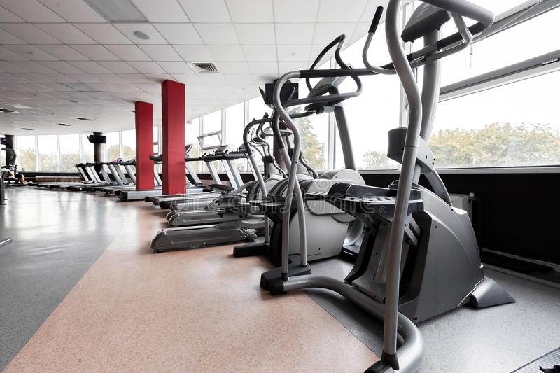 Gym interior with modern elliptical trainers stock photography