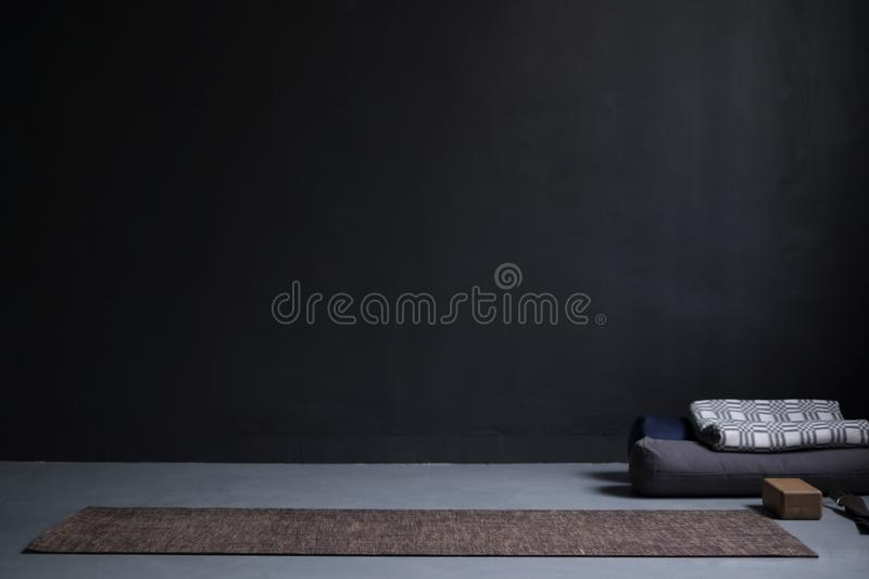 Gym interior with yoga mat and props. no people. Copy space on black wall royalty free stock photography