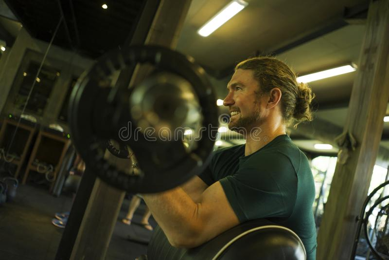 Gym lifestyle portrait of young athletic and attractive man smiling happy and natural training biceps muscle pulling weight bar at royalty free stock images