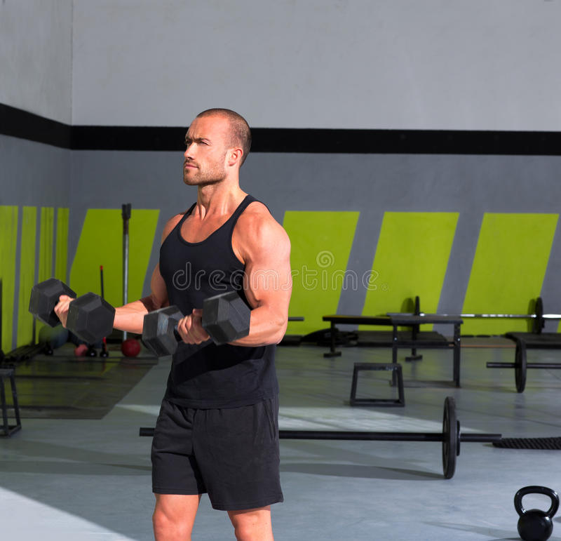 Gym man with dumbbells exercise crossfit. Gym man with dumbbells weights lifting exercise crossfit fitness workout stock photo