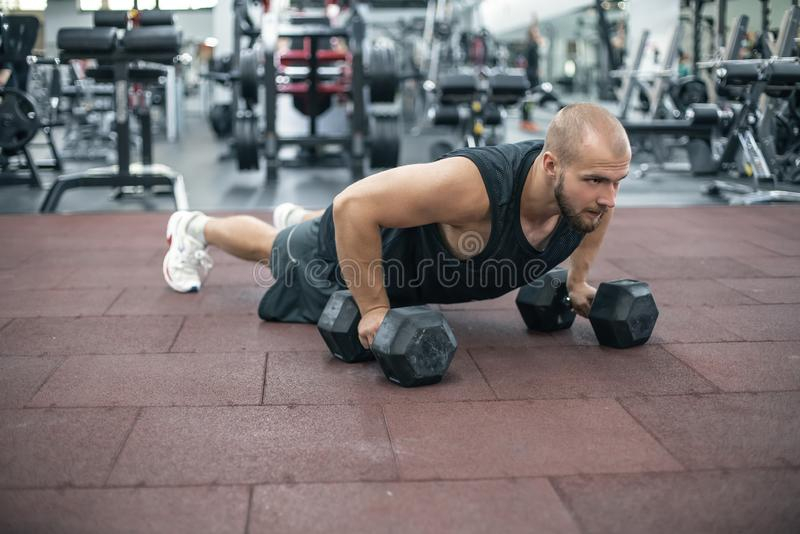 Gym man push-up strength pushup exercise with dumbbell in a fitness workout.  stock photos