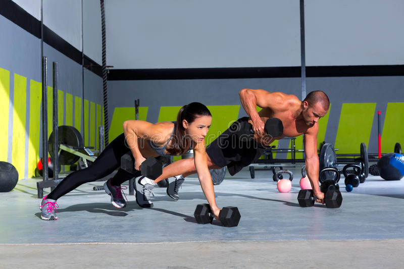Gym man and woman push-up strength pushup. With dumbbell in a crossfit workout stock images