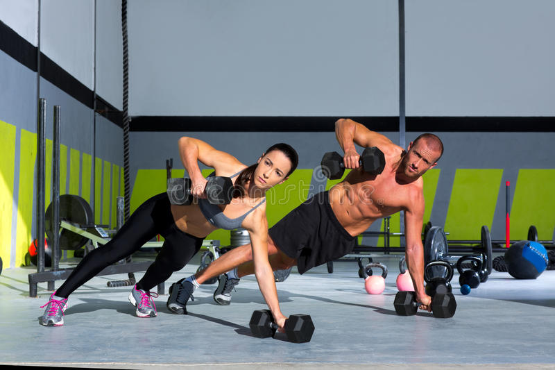 Gym man and woman push-up strength pushup. With dumbbell in a crossfit workout royalty free stock photo