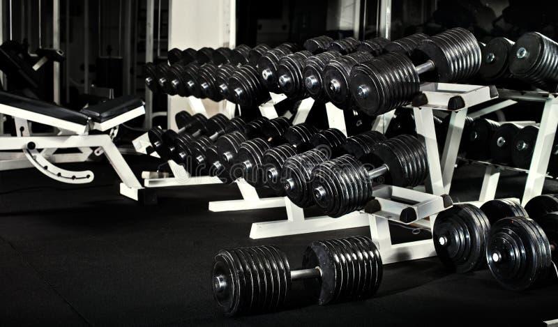 Gym. Many black dumbbells in dark weight room, horizontal photo stock image