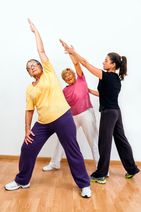 Gym monitor helping senior ladies with exercise. Close up portrait of fitness instructor helping senior ladies with stretching exercise in health club stock images