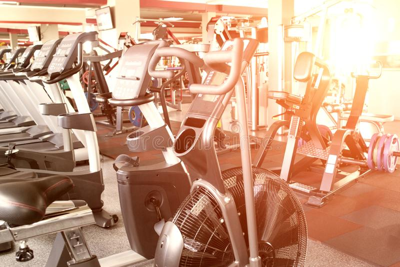 Gym with new modern cardiovascular and weight training equipment, exercise bikes and elliptical trainers, sunset, background royalty free stock image