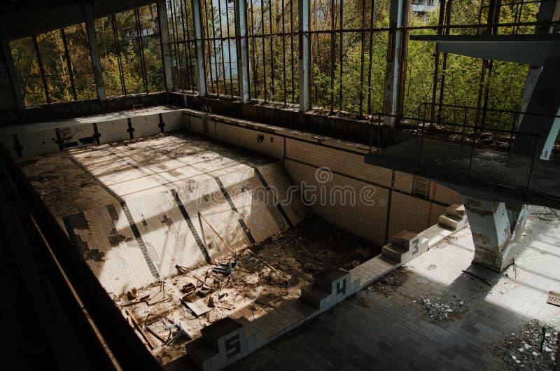 Gym perdido do esporte da escola com piscina na zona da cidade de Chernobyl imagem de stock