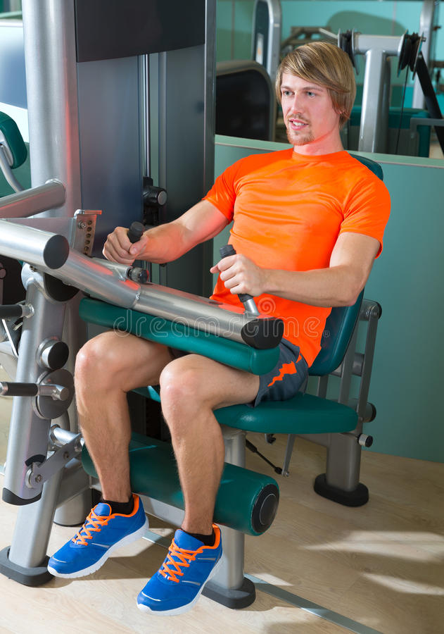 Gym seated leg curl machine exercise blond man. At indoor royalty free stock photo