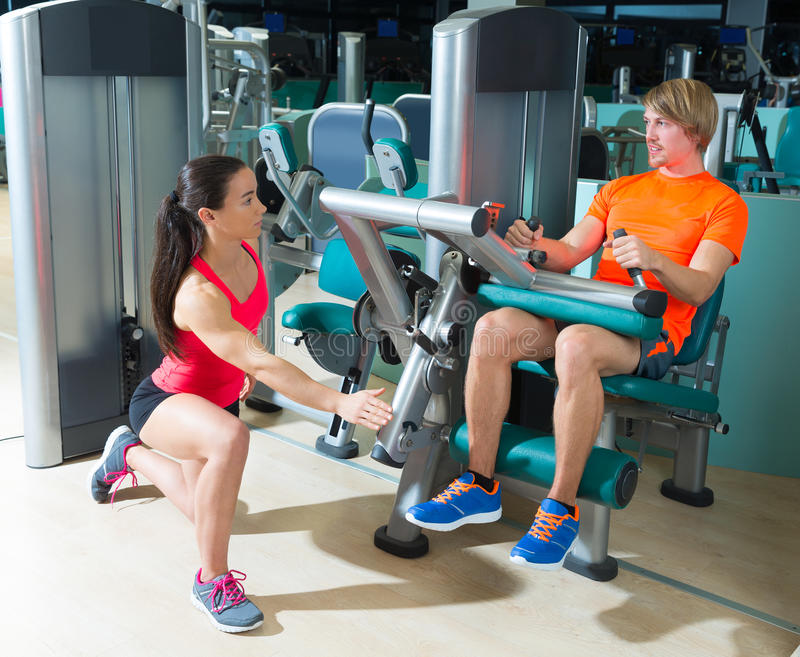Gym seated leg curl machine exercise blond man. Gym seated leg curl machine exercise blond men and personal trainer woman royalty free stock images