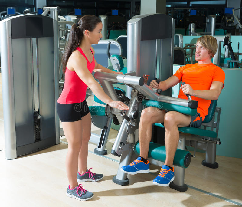Gym seated leg curl machine exercise blond man. Gym seated leg curl machine exercise blond men and personal trainer woman stock image