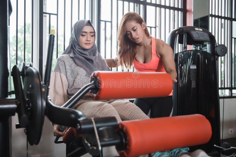 Gym seated leg curl machine exercise muslim women hijab. And personal trainer woman stock photos
