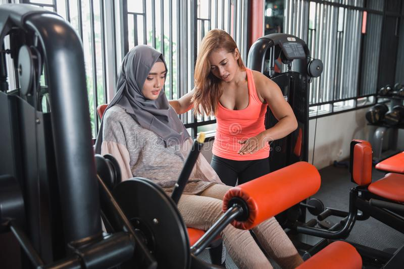 Gym seated leg curl machine exercise muslim women hijab. And personal trainer woman royalty free stock photo