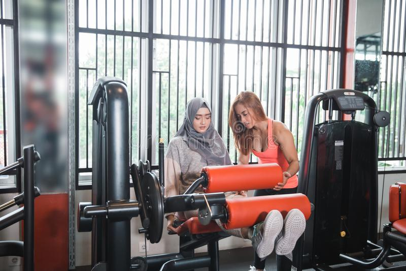 Gym seated leg curl machine exercise muslim women hijab. And personal trainer woman stock photo