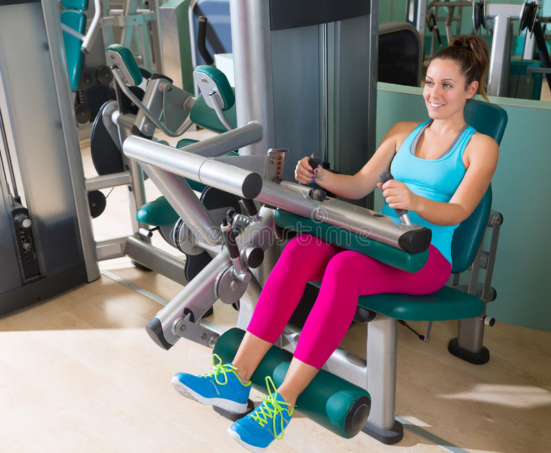 Gym seated leg curl machine exercise woman. At indoor stock photos