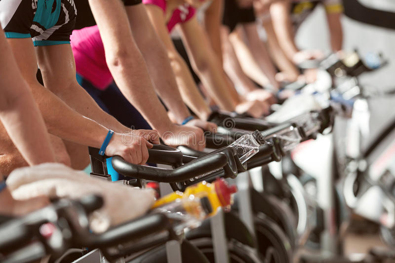 Gym shot - people cycling; spinning class stock images