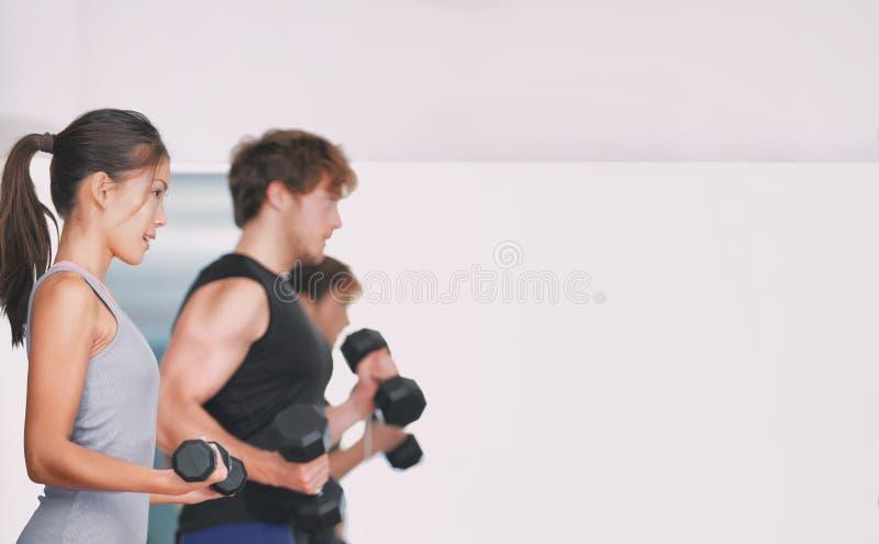 Gym sprawności fizycznej stażowi ludzie podnosi ciężary w weightlifting grupy klasie w studiu obrazy stock