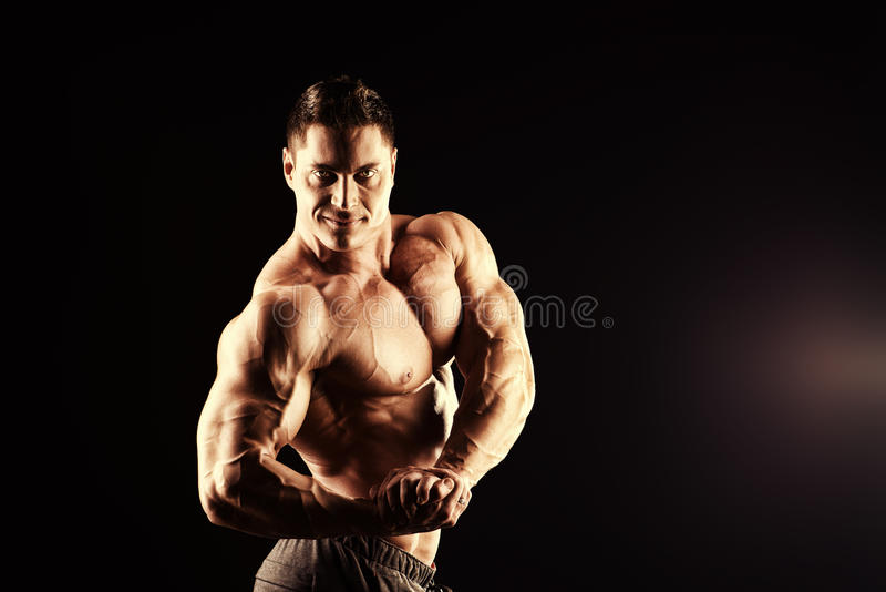 Gym training. Handsome muscular bodybuilder posing over black background royalty free stock photography