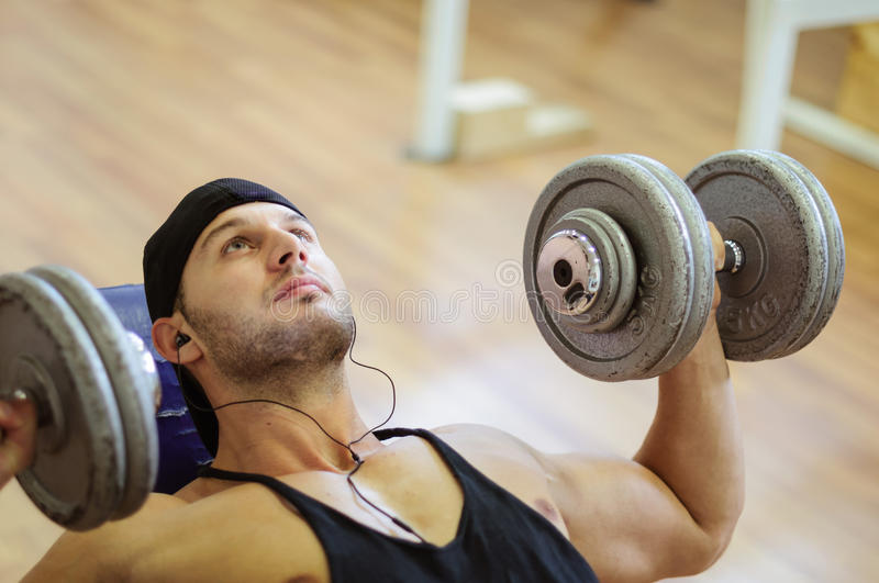 Gym training workout. Young adult man is working out in gym royalty free stock photo