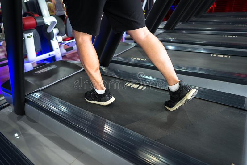 Gym treadmill closeup with man legs running. Concept for exercising, fitness and healthy lifestyle stock photography