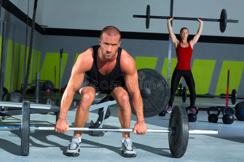 Gym with weight lifting bar workout man and woman. Gym man and woman with weight lifting bar workout in crossfit exercise stock photo