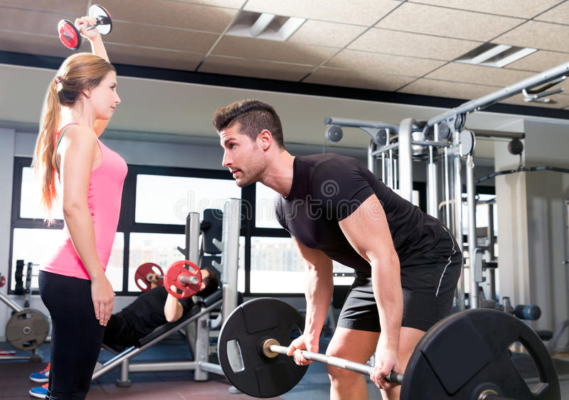 Gym weightlifting couple workout barbell dumbbell stock