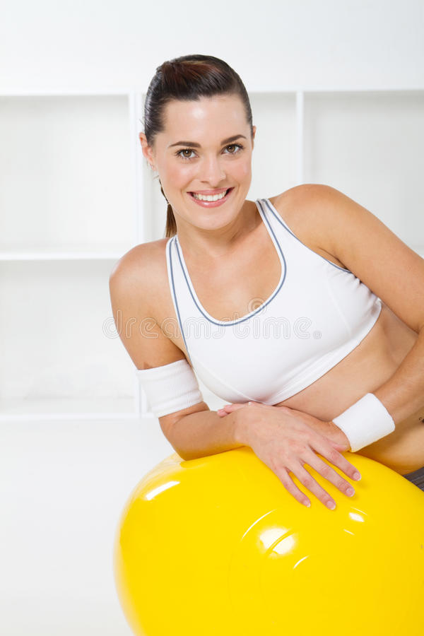 Gym woman. A pretty young gym woman leaning on a yellow exercise ball and smiling stock photo