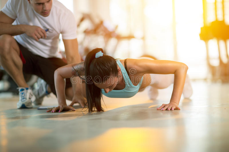 Gym woman doing push ups. Gym women doing push ups with assisting her personal trainer stock images