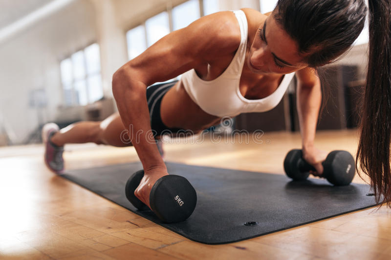 Gym woman doing pushups on dumbbells. Gym woman doing push-up exercise with dumbbell. Strong female doing crossfit workout stock image