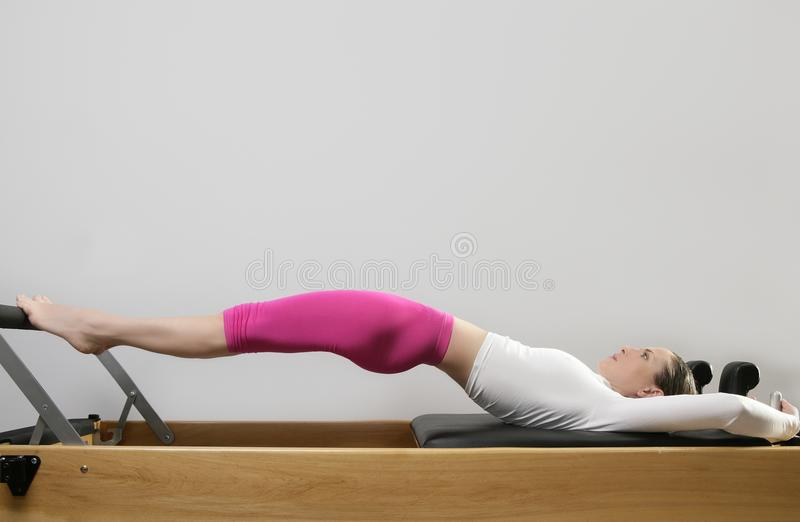 Gym woman pilates stretching sport in reformer bed. Instructor girl stock photo