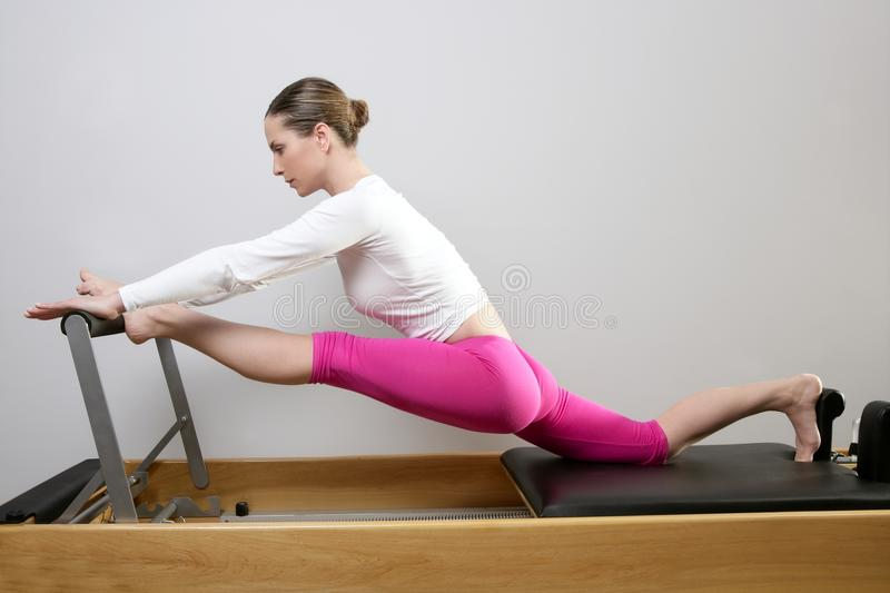 Gym woman pilates stretching sport in reformer bed. Instructor girl royalty free stock photography
