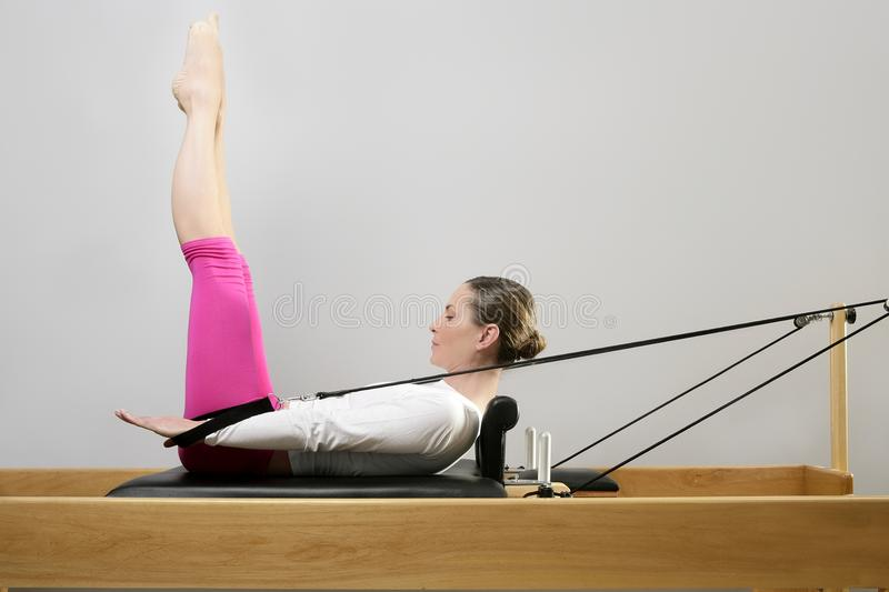 Gym woman pilates stretching sport in reformer bed. Gym woman pilates instructor stretching in reformer bed stock photography
