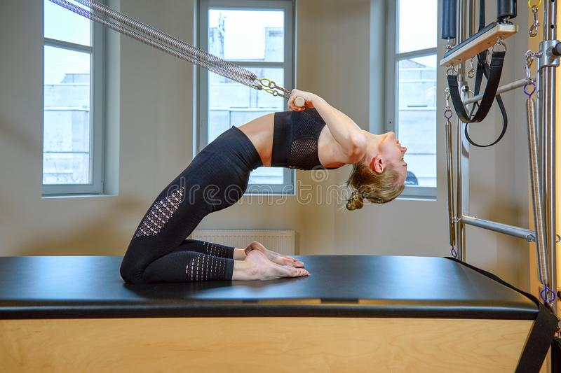 Gym woman pilates stretching sport in reformer bed instructor girl. Healthy Smiling Woman Wearing Leotard Practicing stock images