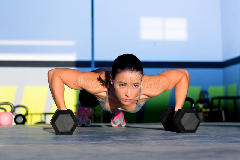 Gym woman push-up strength pushup with dumbbell. Gym woman push-up strength pushup exercise with dumbbell in a crossfit workout royalty free stock photography
