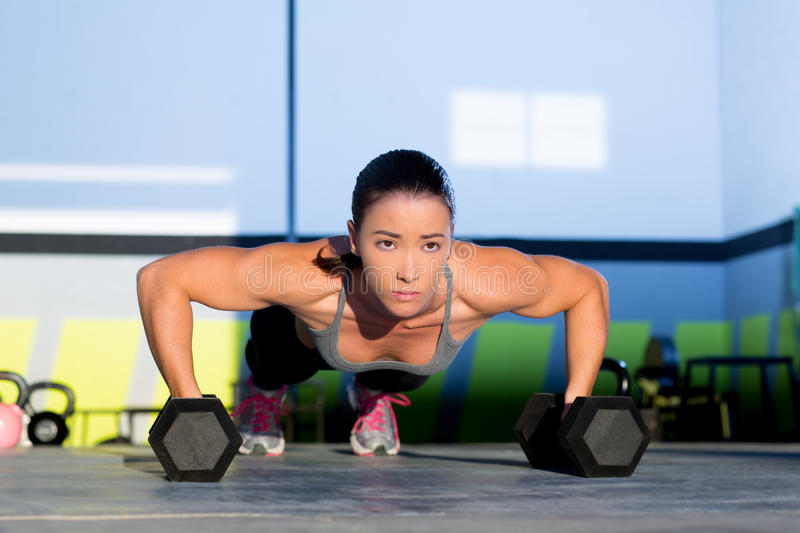 Gym woman push-up strength pushup with dumbbell. Gym woman push-up strength pushup exercise with dumbbell in a crossfit workout stock photography