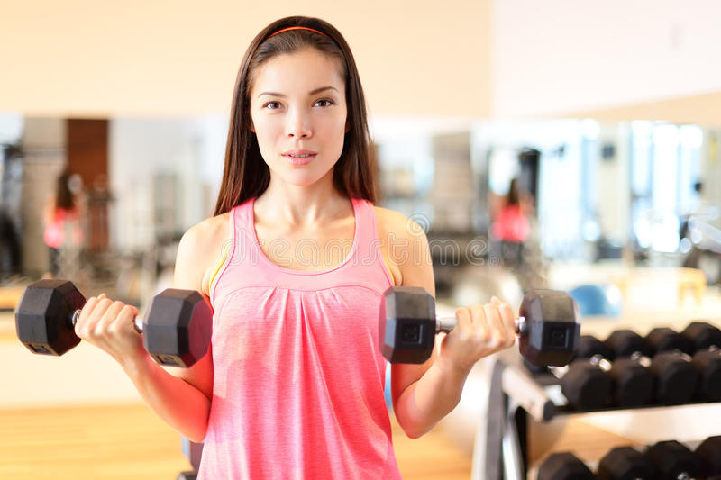 Gym woman strength training lifting weights. Gym woman strength training lifting dumbbell weights in biceps curl exercise. Female fitness girl exercising indoor stock photography
