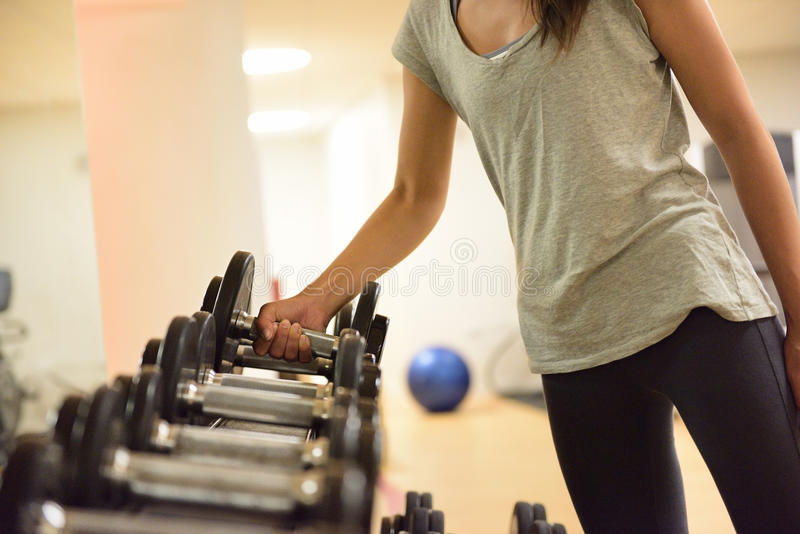 Gym woman strength training lifting weights. Gym woman strength training lifting dumbbell weights getting ready for exercise workout. Female fitness girl royalty free stock image