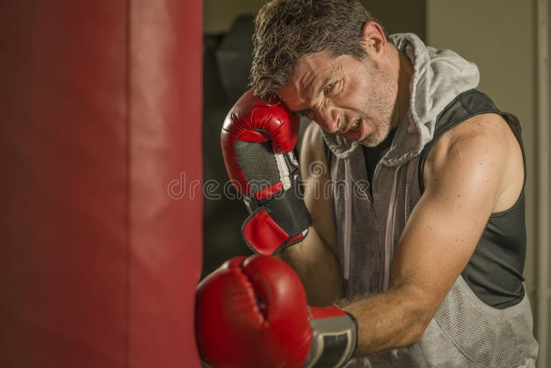 Gym workout portrait of attractive and fierce looking boxer man 30s to 40s in boxing gloves training at fitness club punching stock image