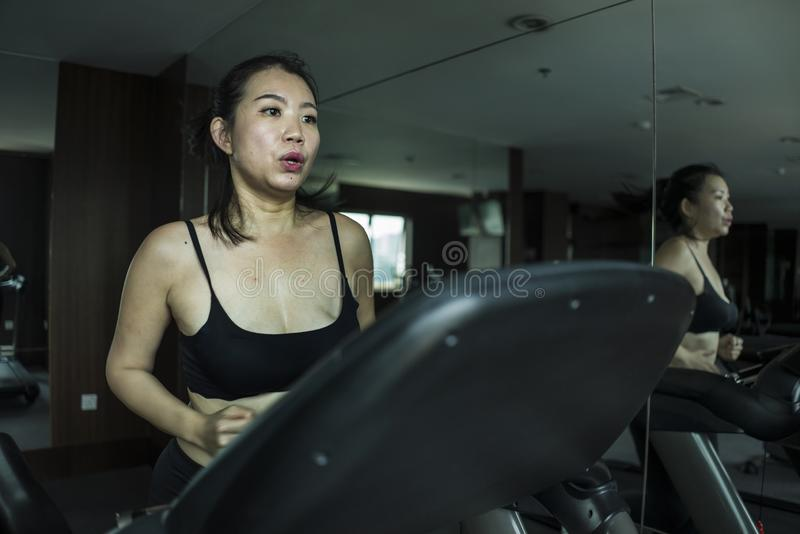 Gym workout portrait of young beautiful and sporty Asian Chinese woman running at fitness club jogging in treadmill training in. Healthy lifestyle and body care stock photos