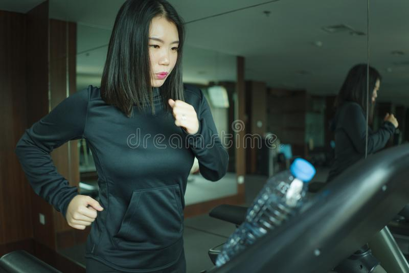 Gym workout portrait of young beautiful and sporty Asian Korean woman running at fitness club jogging in treadmill training in. Healthy lifestyle and body care royalty free stock image